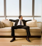 Picture of a man sitting on a sofa. The man seems to be bored.  His arms are out resting on the back of the couch or sofa. His feet on on the floor and his knees spread far apart. The man appears to be waiting for something.